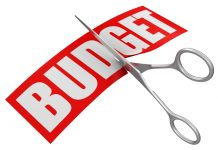 The word budget being cut in half with scissors