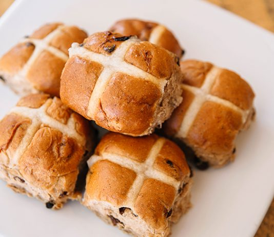 Six hot cross buns on a white, square plate.