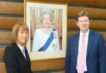 Irene Lucas posing in front of portrait of Queen Elizabeth