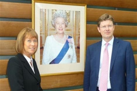 Irene Lucas posing in front of portrait of Queen Elizabeth