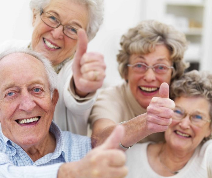 Four elderly people smiling and giving thumbs up.