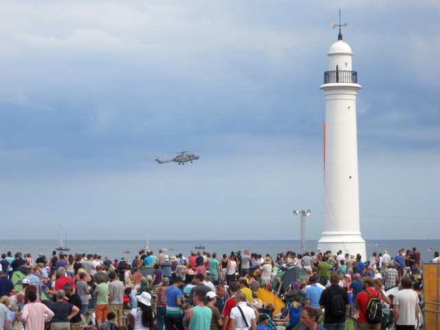 A helicopter flying over the sea towards a lighthouse, above a crowd of people.