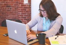 Woman in thick glasses using a laptop with poor posture and a full cup of tea right next to it, with papers on the other side of the tea.